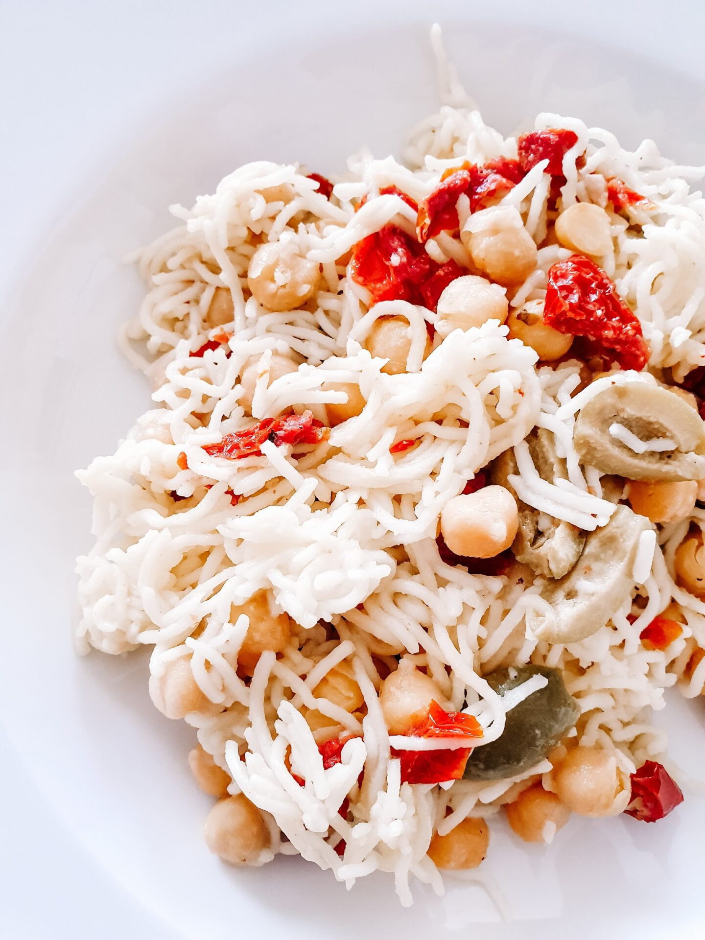 photo of a noodle salad in a bowl with chickpeas and sundried tomatoes.